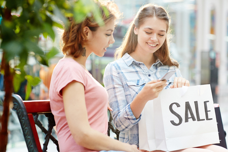 Two happy shoppers ordering something to eat after hard shopping in the mall Stock Photo