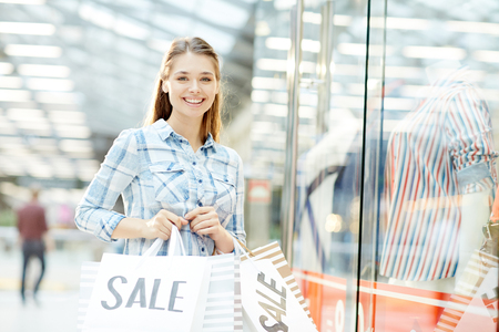 Modern custmer with paperbags standing by large window-display during shopping in trade center Stock Photo