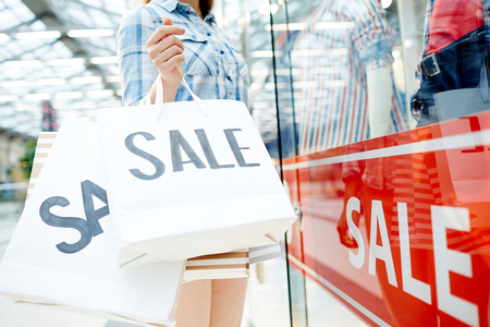 De klant houdt papieren zakken met verkoopaankondiging terwijl status door venstervertoning in modern winkelcentrum Stockfoto - 87124694