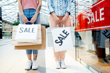 Two friends with paperbags made purchases in mall departments during seasonal sale Stock Photo
