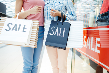 Jonge vriendelijke vrouwen in casualwear met boodschappentassen na zwarte vrijdagverkoop