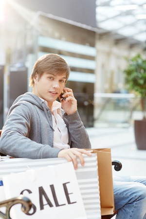 Mobile guy with purchases speaking on smartphone while having rest after shopping