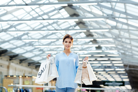 Happy girl in casualwear holding paperbags with gifts bought on sale Stock Photo