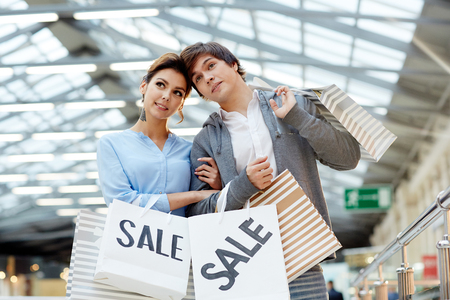 or spree: Affectionate dates with paperbags shopping in large modern trade center during sale Stock Photo
