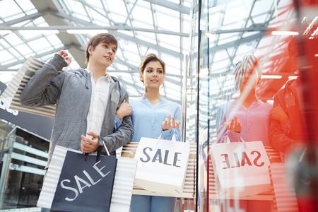 Jong koppel met aankopen op zoek naar stijlvolle kleding in het raam Stockfoto - 87124706