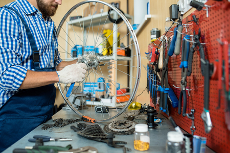 Repairman standing by his workplace and tightening bolt on bicycle wheel