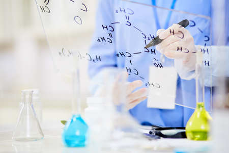 Unrecognizable chemist writing down structural formula on glass board while focused on work at modern laboratory, blurred background