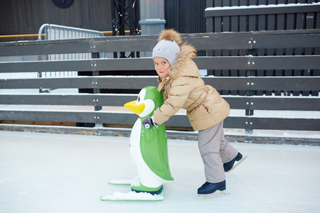 Child skating with green toy penguin