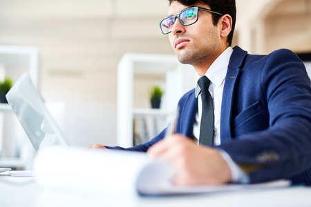 Pensive financier working in office Stock Photo
