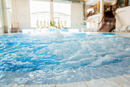 Waves and splashes in warm spa jacuzzi with nobody around Stock Photo