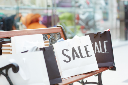 Several paperbags with purchases on bench with nobody around in modern mall
