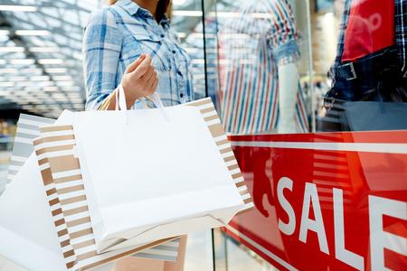 Vrouwelijke shopper bedrijf papiertassen tijdens het bezoeken van grote moderne winkelcentra tijdens de verkoop