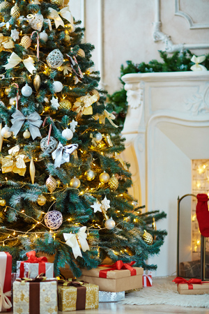 Christmas tree decorated with bubbles, bows and stars and heap of gifts near by