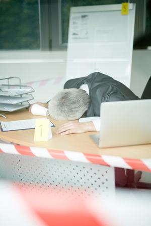 Crime scene through panoramic window: lifeless senior businessman in classical suit lying on office desk, striped crime scene tape
