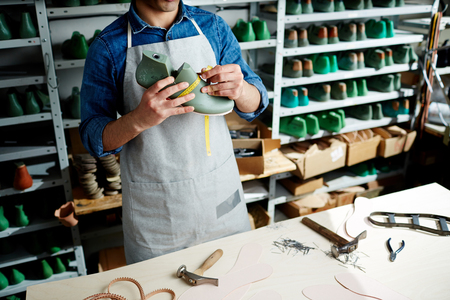 Young cobbler in uniform taking measures of shoe model over his workplace