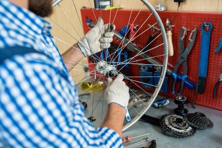 車輪の中央歯車を固定する自転車修理工の手袋の手