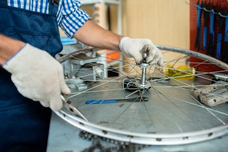 自転車の車輪の部品をチェックする手持ちなどの修理工 写真素材