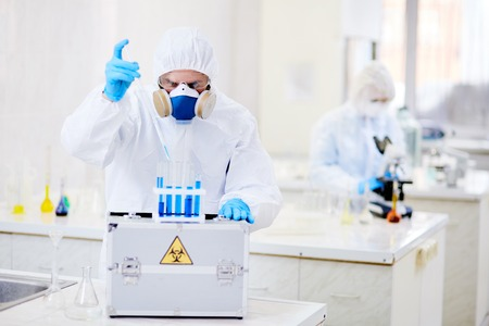 Scientist dropping liquid substance into flask with toxic fluid