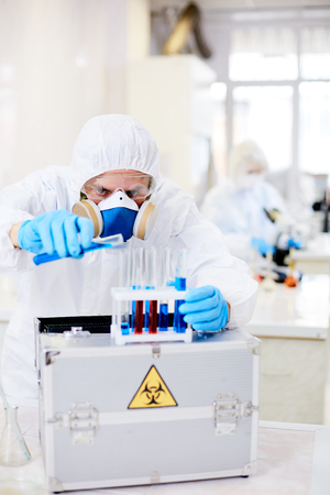 Man in protective hazmat, gloves and respirator mixing two liquids in clinical lab