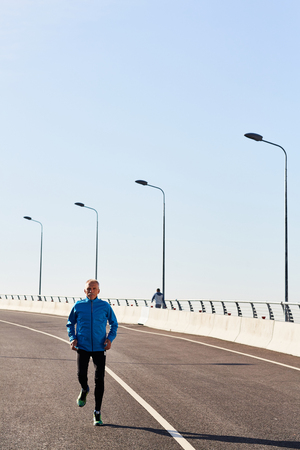 Aged man in sportswear jogging on roadway in urban environment
