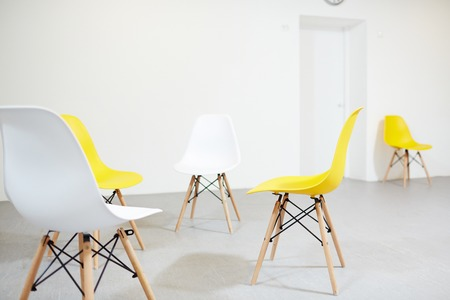 Four plastic chairs of white and yellow colors in empty classroom of modern school Foto de archivo