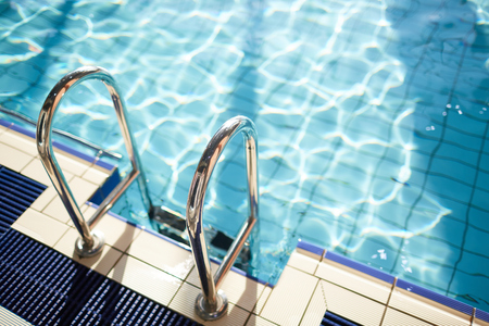 Steel railings by edge of swimming pool with pure water