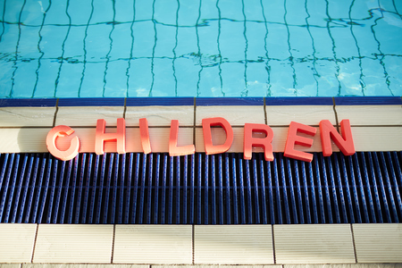 Word children formed up on the floor of swimming-pool by edge of water Imagens