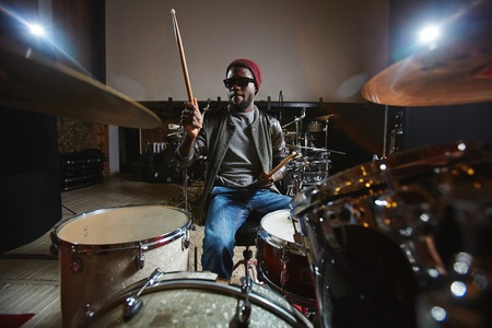 Contemporary and popular African-american musician playing drums during repetition