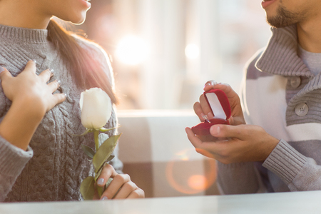 Amazed girl with romantic white rose and small open jewellery box with engagement ring in man hands Stockfoto