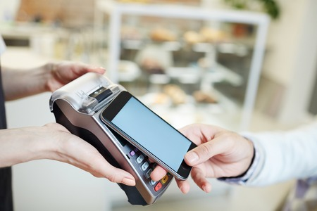 Contemporary client of cafe making contactless payment after lunch Stock Photo - 93395945