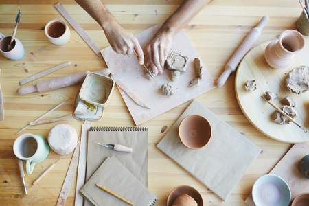 Overview of human hands with knife cutting pieces of clay on wooden board before making new toys or earthenware Stock fotó