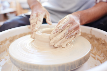 Hands of potter on rotating fireclay machine creating new earthenware Фото со стока