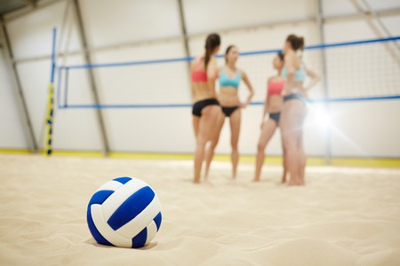 Volleyball ball on sandy fiels and group of female players talking on background