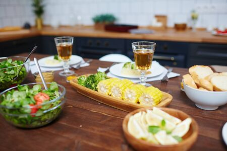 Tasty homemade salad, corn and drinks in wineglasses served for guests