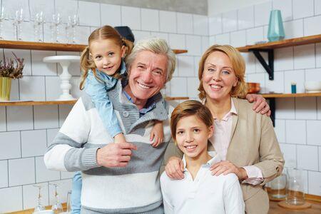 成熟した男性の幸せな家族、彼の妻とカメラを見て彼らの2人の孫