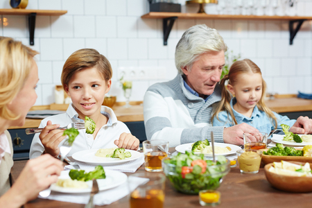 Cute boy eating broccoli and talking to his grandmother by festive table Banco de Imagens