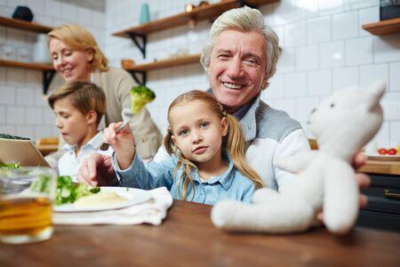 彼の孫娘がおもちゃを供給しながら、テディベアを見て幸せな祖父