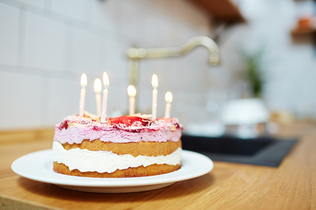 Fresh and tasty homemade birthday cake with burning candles on table