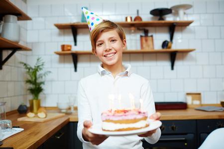 Glücklicher Junge mit toothy Lächeln , Geburtstagskuchen zu halten und Kamera zu Hause betrachten Standard-Bild - 93757067