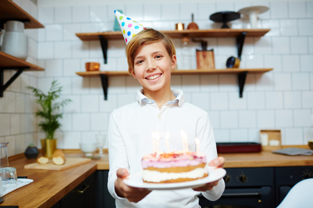Menino feliz com sorriso segurando o bolo de aniversário e olhando para a câmera em casa Foto de archivo - 93757067