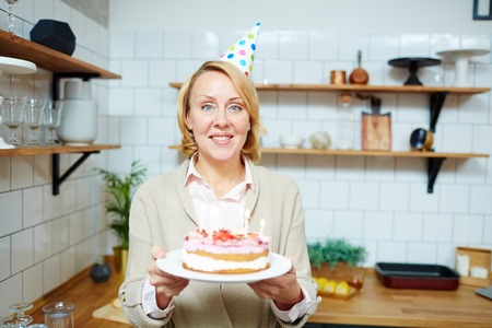 Smiling woman in birthday cap holding self-made cake for her guests 版權商用圖片