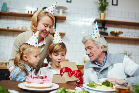 誕生日キャップの小さな男の子は、近くに彼の妹や祖父母とギフトボックスで彼のプレゼントを見て