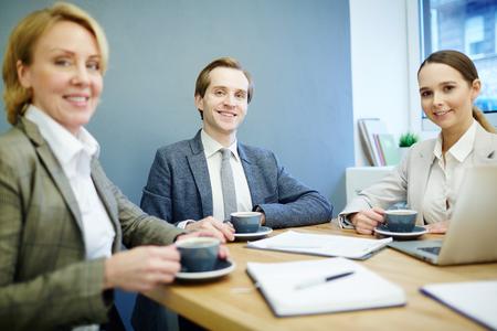 Equipo de líderes exitosos sentados por el lugar de trabajo en la oficina y mirándote Foto de archivo - 93743928