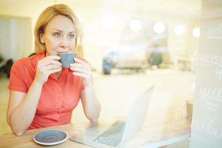Madura loira beber café quente da caneca cinza no café e olhando pela janela Foto de archivo - 93756966