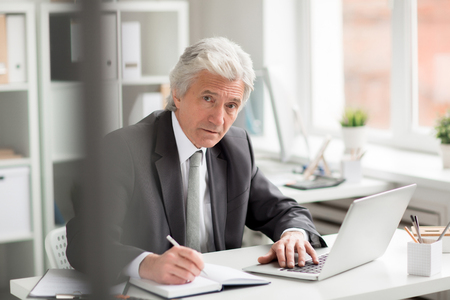 Experienced director in formalwear sitting by workplace, networking and making notes