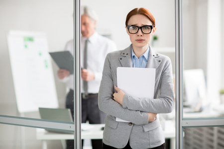 Scared employee with documents standing by door of her boss office and going to talk to him