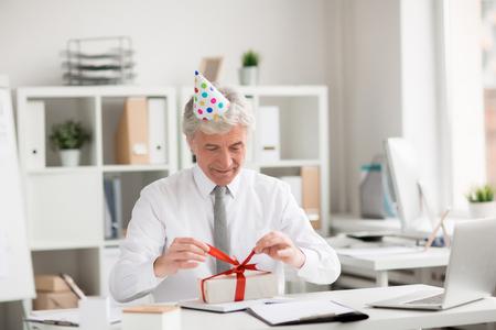 Uomo d'affari senior felice in nastro sciogliente del compleanno-cappuccio sopra il contenitore di regalo in ufficio Archivio Fotografico - 93743766