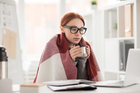Młoda kobieta w kratę i okulary, picie gorącej herbaty z kubka podczas pracy w biurze Zdjęcie Seryjne
