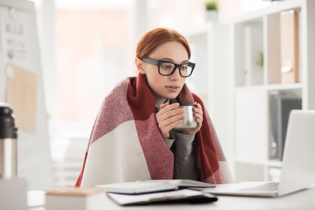 Young woman in plaid and eyeglasses drinking hot tea from mug during work in office