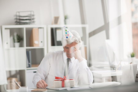 Senior man in formalwear sitting by workplace in office and looking at box with his birthday present